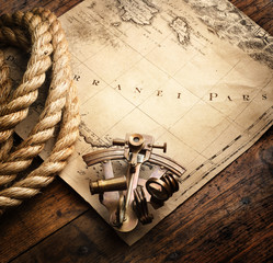 Fototapete - Astrolabe and rope on vintage map. Adventure stories background.