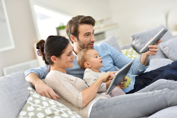 Family with baby in sofa watching tv
