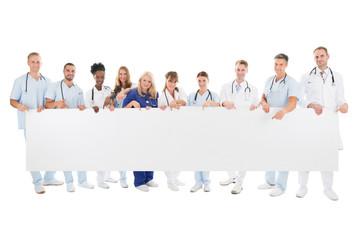Confident Multiethnic Medical Team Holding Blank Billboard