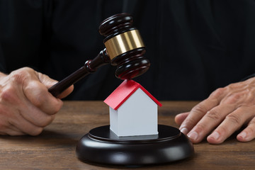 Judge Holding Gavel On House At Desk