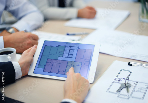 Real Estate Agent Showing House Plans On Electronic