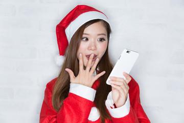スマートフォンを見て驚くサンタの女性