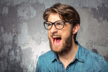Young man screaming with widely opened mouth