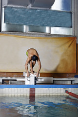 Young muscular swimmer in low position on starting block in a sw