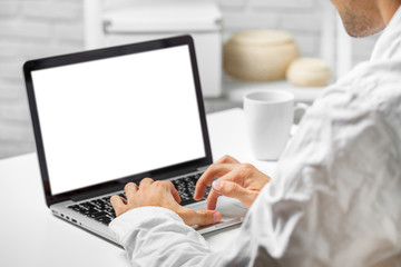 Cropped shot of a man's hands using a laptop at home