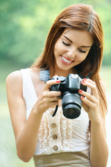 portrait of young beautiful brunette woman holding photocamera