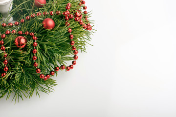 Christmas wreath and candle on white background, close up