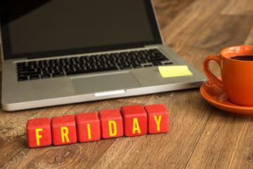 Friday written on a wooden cube in a office desk