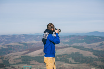 Man with a camera at the edge of a cliff overlooking the mountai