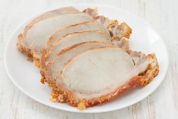 baked pork on white plate on white wooden background
