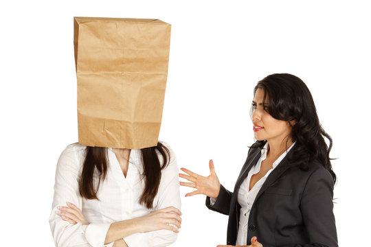 Two businesswomen. One talking in frustration, the other has a bag over her head.