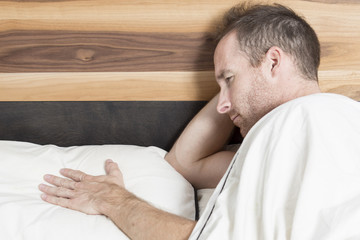Bright shoot of upset man lies in the bed
