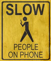 slow people on phone sign on wood grain texture
