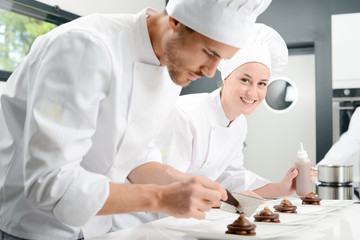 portrait of a cheerful young woman professional pastry cook at work in kitchen decorating a chocolate dessert