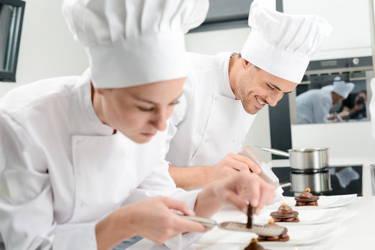 pastry cook professional team man and woman in restaurant kitchen preparing a chocolate dessert