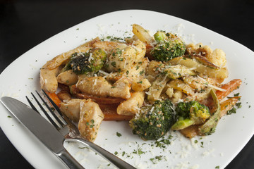 Chicken with vegetables in a white plate