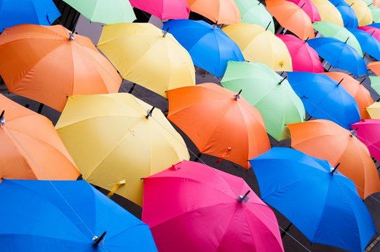 Many colorful umbrellas in city settings. Kosice, Slovakia. Top view. Color background