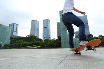 young woman skateboarder skateboarding on city