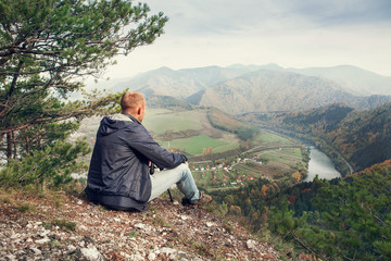 Man sitting on the edge of the cliff above mountaine valley