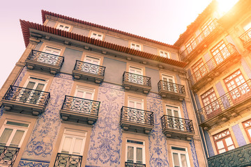 Facades of typical old town houses in Portugal - Traditional and colonial building concept - Vintage editing with artificial sunlight