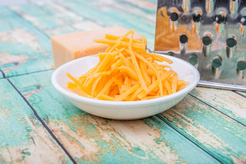 Grated cheddar cheese with steel grater over wooden background