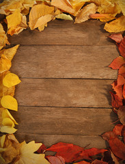 Colourful frame of autumn leaves, on wooden background