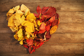 Colourful autumn leaves in the shape of heart, on wooden background