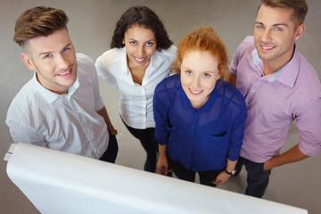 gruppe arbeitet am flipchart und schaut lächelnd nach oben