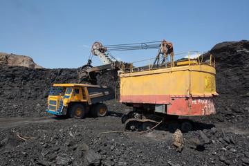 Coal mining. The dredge loads the truck coal.