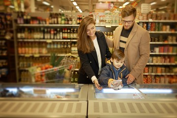 Young family near freezer in a grocery store