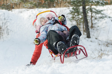 Excited sibling children laughing during sledding down snowy hill by wooden sled