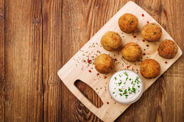 Chickpea falafel balls on a wooden desk with vegetables