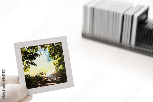 Gloved hand holding a framed strip of slide film with a stack of ...