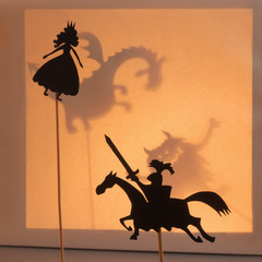 Princess and Knight shadow puppets. Bright yellow glowing screen of shadow theatre with two monsters shadows in the background.