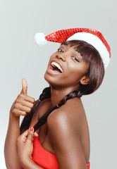 Happy black woman portrait closeup, emotion facial expression. Chocolate shiny hair and black and white christmas hat on her head.