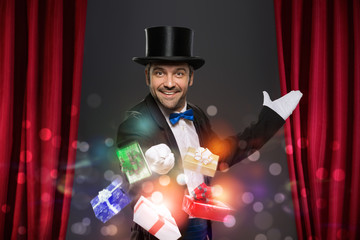 Wall Mural - Cheerful magician performs the trick with magic box