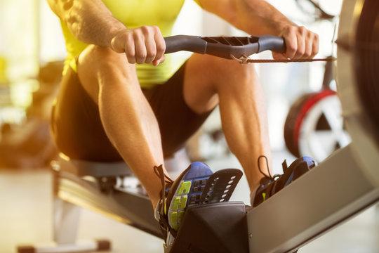 man training on row machine in gym