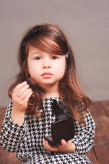 Beautiful baby girl 3-4 year old applying powder on face in room. Looking at camera. Wearing stylish dress.