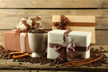 Beautiful gifts with bows and coffee grains on wooden background
