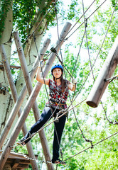 Adventure climbing high wire park - woman on course in mountain