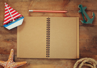 top view image of open blank notebook, wooden sailboat, nautical rope. travel and adventure concept. retro filtered image