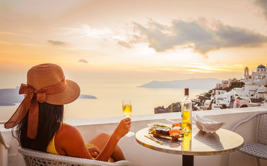 Female tourist enjoying food, wine and sunset view at Santorini, Greece