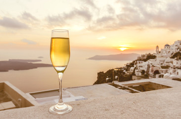 a glass of white wine on balcony with Caldera city view at sunset, yellow sunlight and bright sky before getting dark (selective focus on a glass of wine)