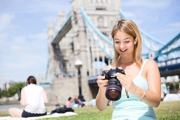 young woman looking at photos on her camera by tower bridge