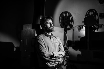 man standing near a film projector in the room projectionist