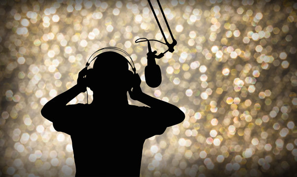 Entertainment background with silhouette of  singing or singer with headphone and microphone on beautiful bokeh  light in party and joyful event night or superstar search contest concept
