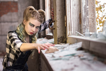Girl in an abandoned building in the broken window