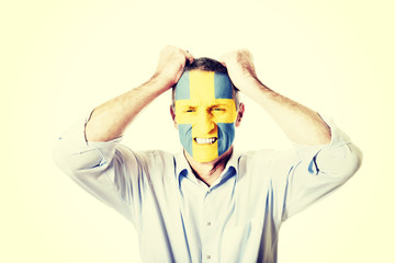 Mature man with Sweden flag on face.