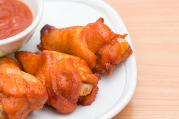 Chicken wings with sauce in dish on wooden table.