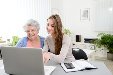 young woman helping an old senior woman doing paperwork and administrative procedures with laptop computer at home